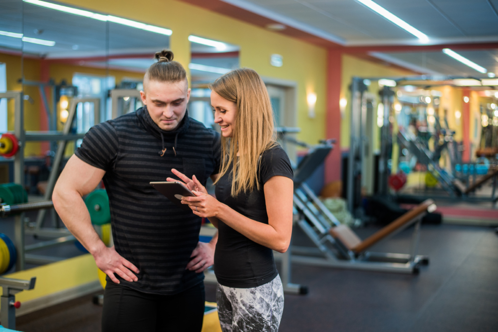 fit attractive young couple at a gym looking at a UDBLVCQ scaled