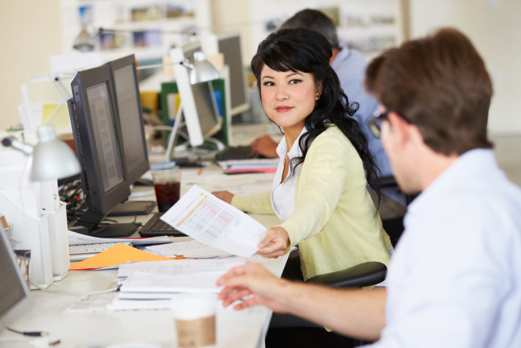 woman working at desk in busy creative office PKC LAM scaled